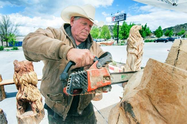Chain-saw sculptor Jerry Stringham of Orderville, Utah, works on a piece featuring two bears hugging. Photo by Shaun Stanley.