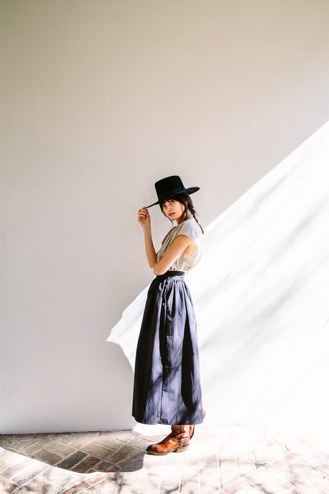 Ranch skirt by Jesse Kamm, top by Caron Callahan and vintage wood-and-shell necklace; all available at Kick Pleat, Austin. Boots by Lucchese. Hat by Stetson.