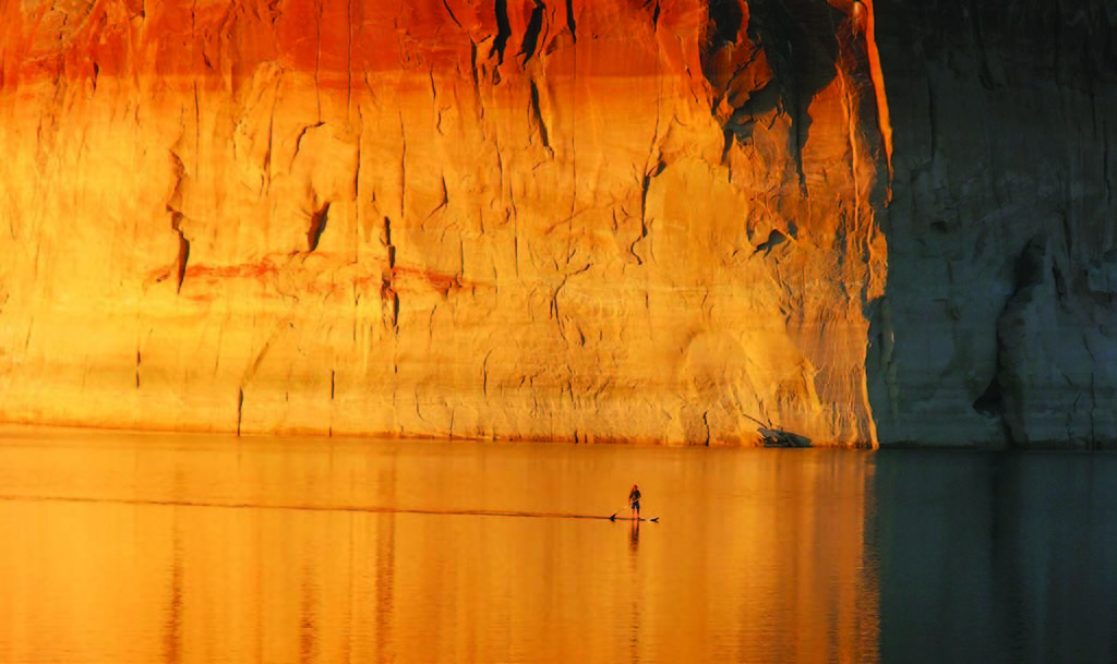 A striking monolith jutting 200 feet from the middle of Lake Powell, Lone Rock dwarfs the occasional paddleboarder.