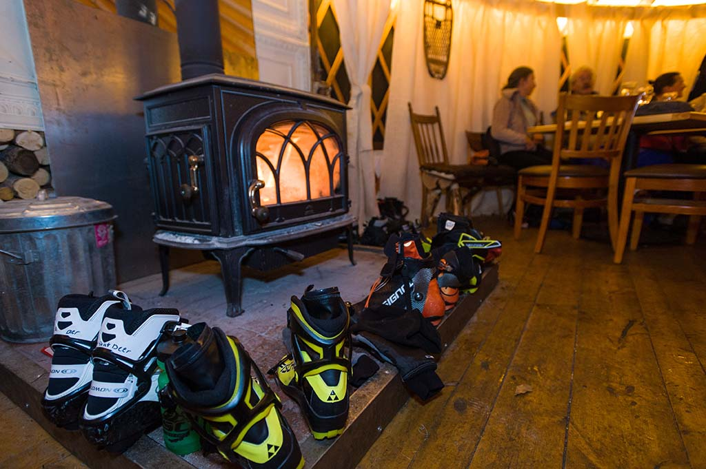 Ski boots warm up by the fire. Photo by Xavier Fane.
