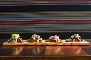 Four of chef David Schmidt's tacos excepcionales at Tii Gavo restaurant: chicken tinga, prime rib, grilled swai with citrus, and slow-cooked pork belly.