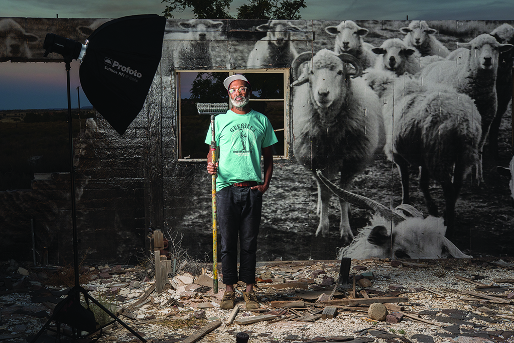 Chip Thomas with his mural at Cow Springs. Photo by Dawn Kish.