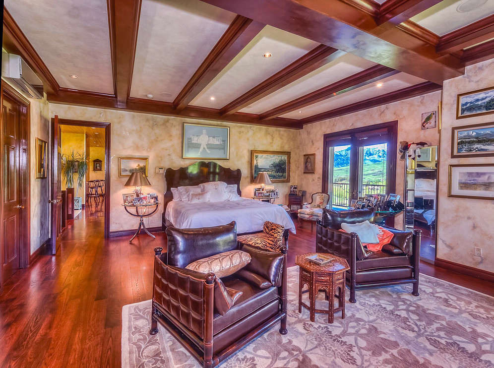 Accented with beautiful wood beams and a hardwood floor, the master bedroom features a gas fireplace, a sitting area and sweeping mountain views. Elegant French doors open up to the back deck.