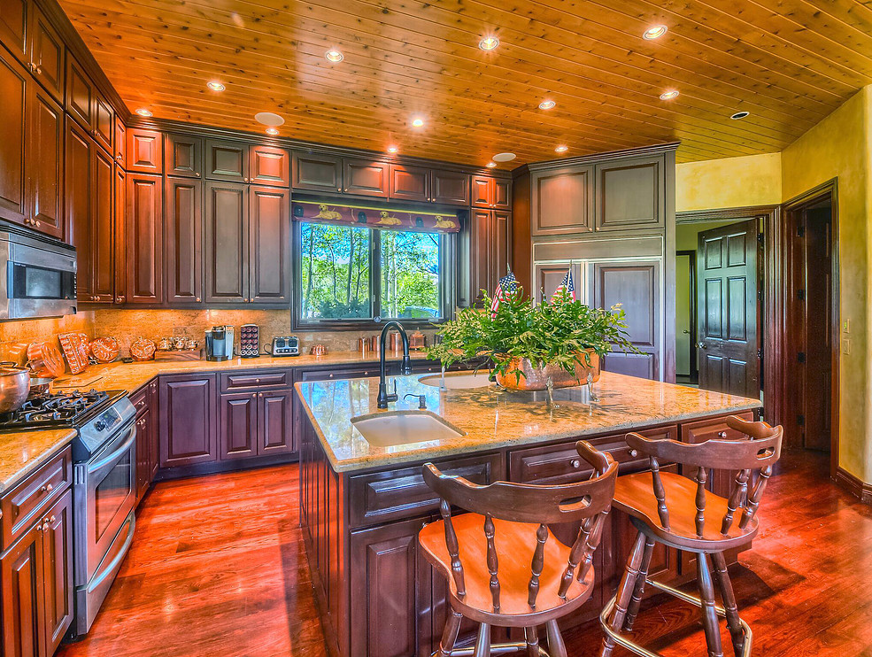 A built-in refrigerator matches rich colors of the cabinets in this open kitchen, which offers access to the garage, laundry and dining and great rooms.