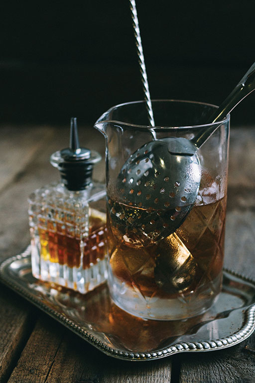 classic manhattan cocktail ingredients in a mixing tumbler on a